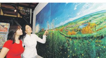Lim explaining an artwork to a visitor